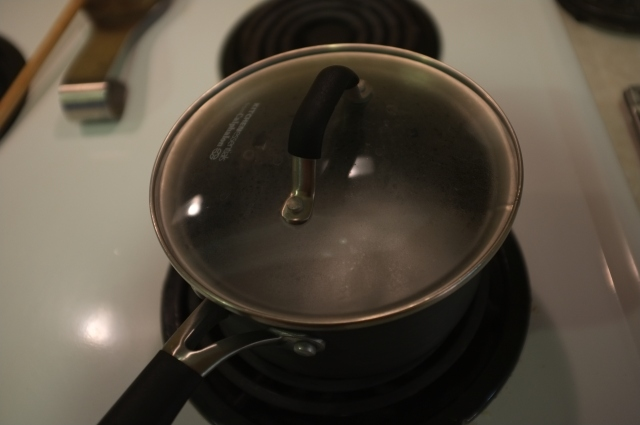 covering it at the early stages of boiling traps the steam and prevents the sugar from crystalizing