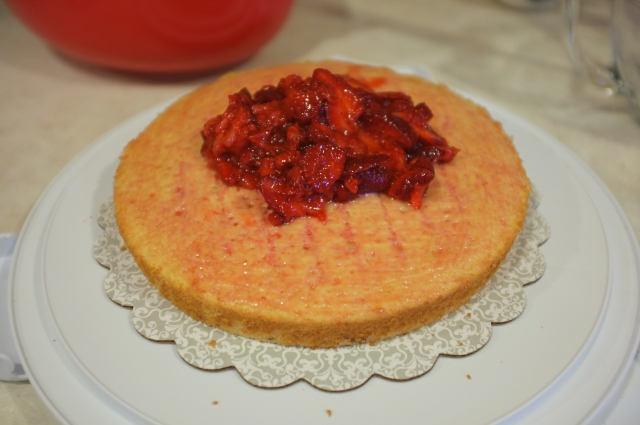After spreading some juice on top of the cake, strawberries get plopped on top…
