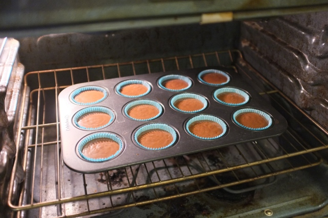 In the oven ready to be baked!  They were filled higher than normal for cupcakes, as recommended by the book.